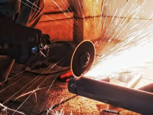 Image of particles being produced from the abrasive wheel of a power tool.